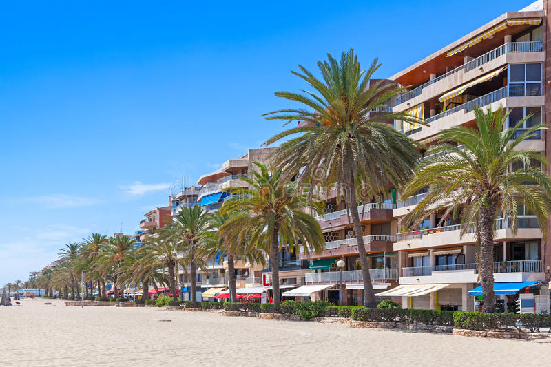 Coastal street of Calafell resort town, Spain. Modern buildings and palm trees on coastal street of Calafell resort town in sunny summer day. Tarragona region stock photos