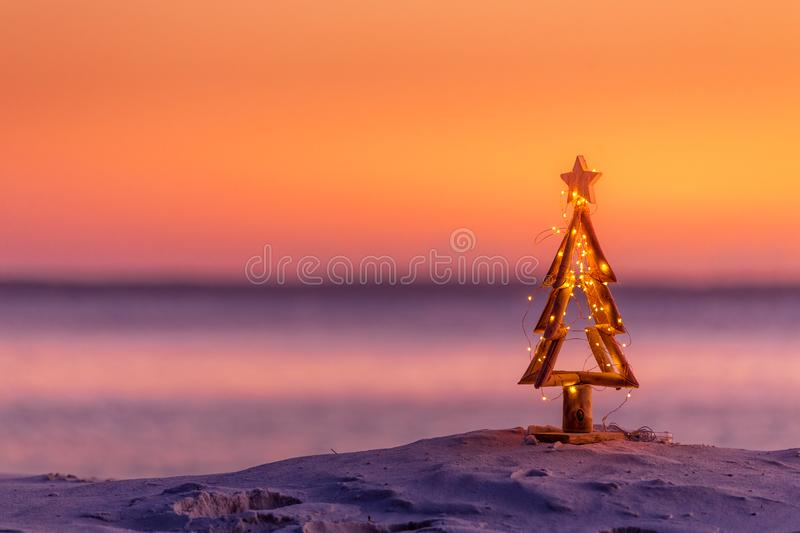 Coastal summer Christmas in Australia. A coastal summer Christmas in Australia.  A driftwood Christmas tree decorated with fairy lights on the beach in summer royalty free stock image
