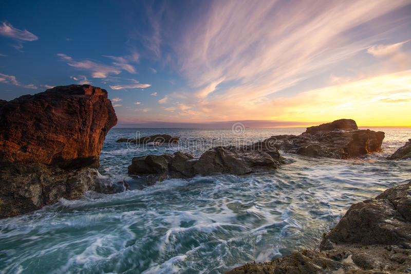 Coastal Sunset. A landscape image of a Coastal scene at sunset. Blue sky and waves crashing over rocks stock photo