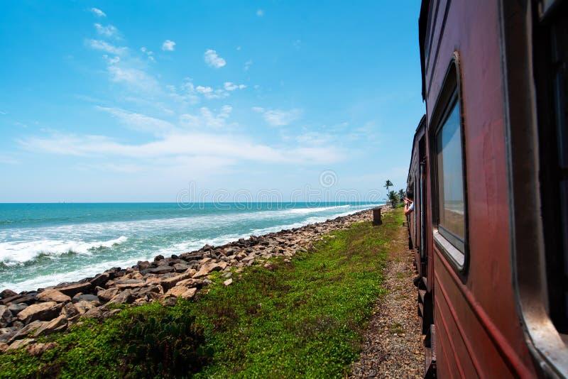 Coastal train in Sri Lanka. Coastal train scenic view in Sri Lanka beach seaside red asia water tropical rail colombo wagon travel transport public tropics royalty free stock photo
