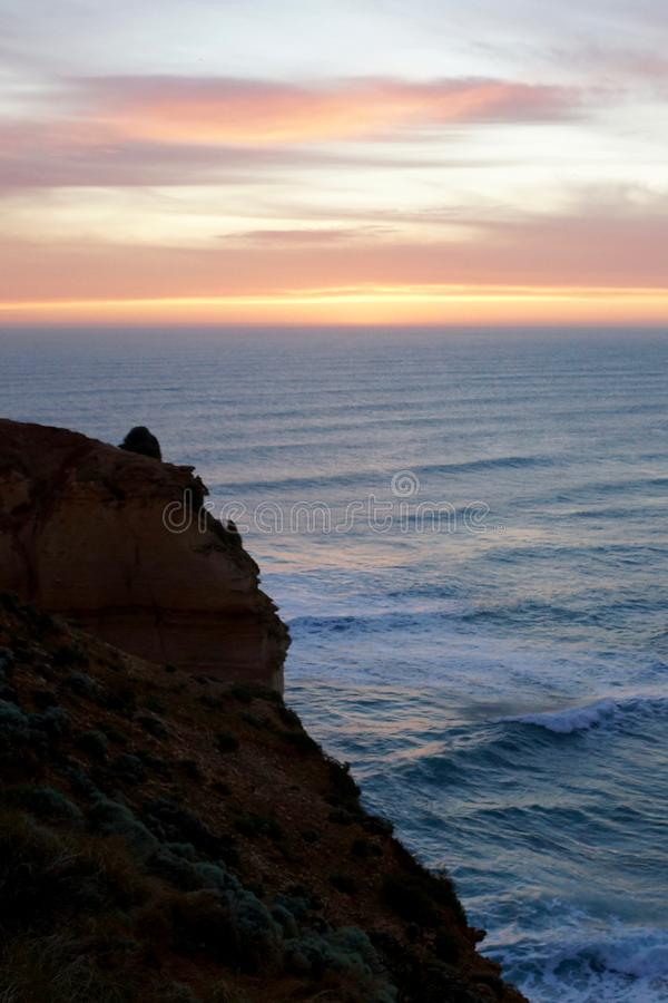 Coastal twilight horizon. Black coastal cliff, view over the ocean at sunset stock image