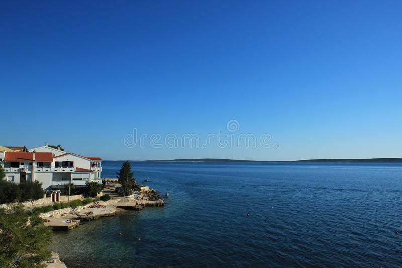 Coastal View with Rocky Beach Resort and Blue Sea. Few Houses With Red Roofs and Wide Blue Sea royalty free stock photos