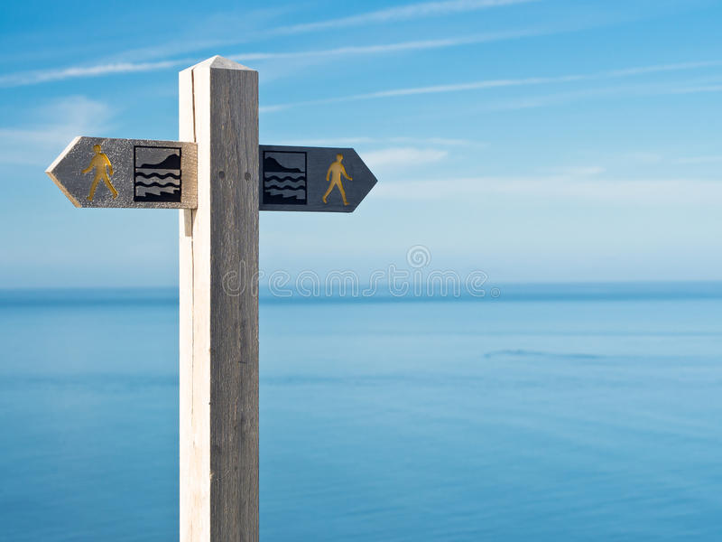 Coastal Walking Path Sign. Signpost for the coastal path in Wales, against a background of blue sea and sky. Wales, UK royalty free stock images