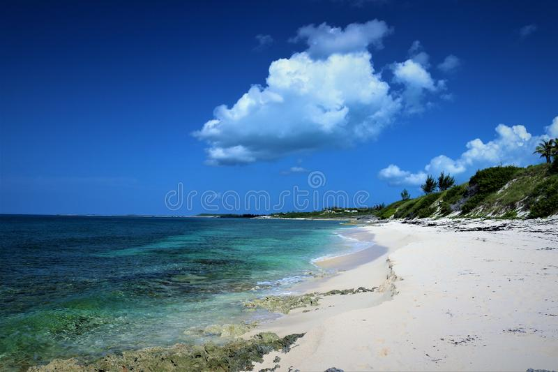 Coastline of the Atlantic Ocean on Eleuthera in the Bahamas. Under bright blue sky with broken clouds. Crystal clear blue green water. sandy beach royalty free stock image