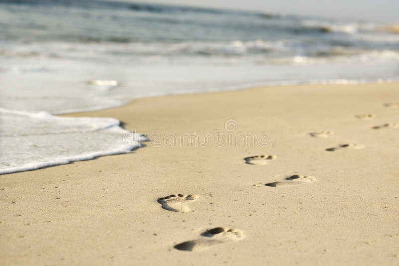 Coastline with footprints and waves. stock photo