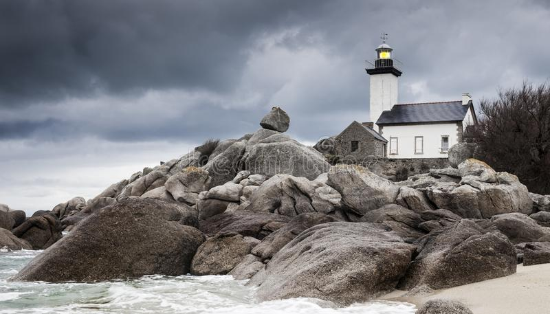 Coastline landscape in low tide with lighthouse and peculiar rocks in Brittany, France stock photo