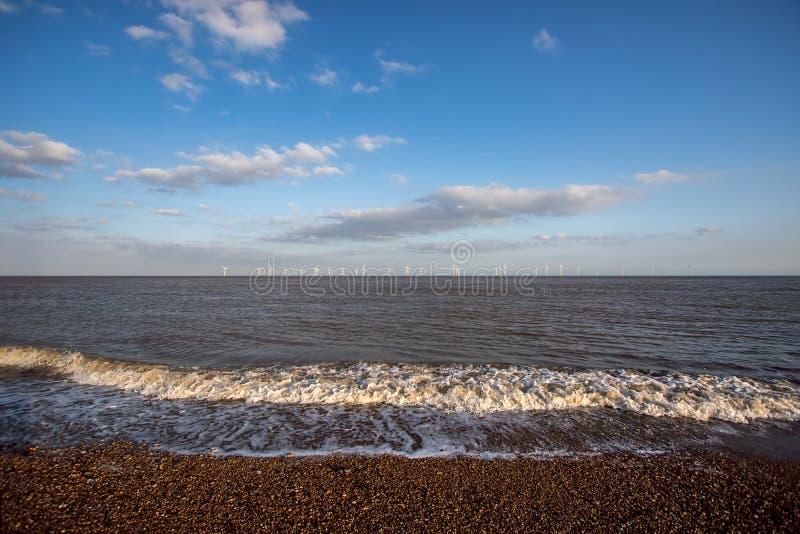 Coastline landscape with offshore wind farm turbines on the horizon. stock image