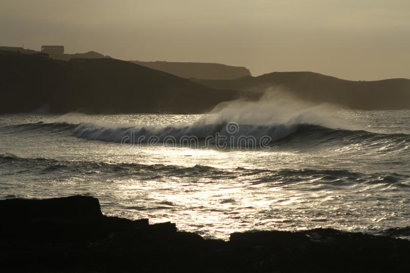 Coastline with rocks, big incoming waves with sea spray during sunset stock images