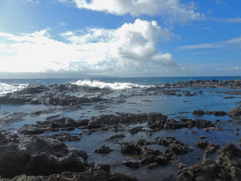 Coastline and rugged lava rocks called Dragon's Teeth and crashing waves at Makaluapuna Point near Kapalua, Maui, HI, USA. Coastline and rugged lava rocks royalty free stock photography