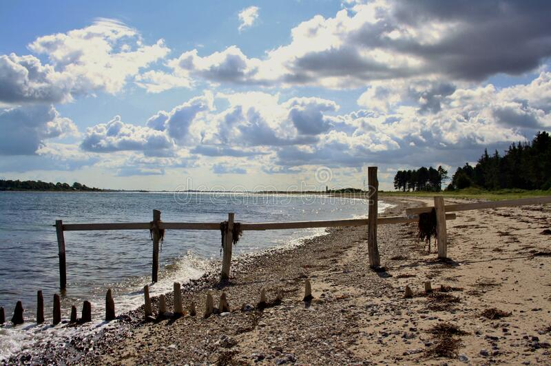 Beach wooden posts clouds stock image
