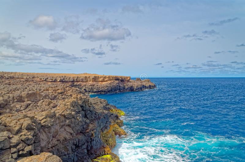 Coastline under cloudy sky. Island Sal, Cape Verde. Scenic view of the coastline cliff and splashing waves of atlantic ocean. Island Sal, Cape Verde stock photography