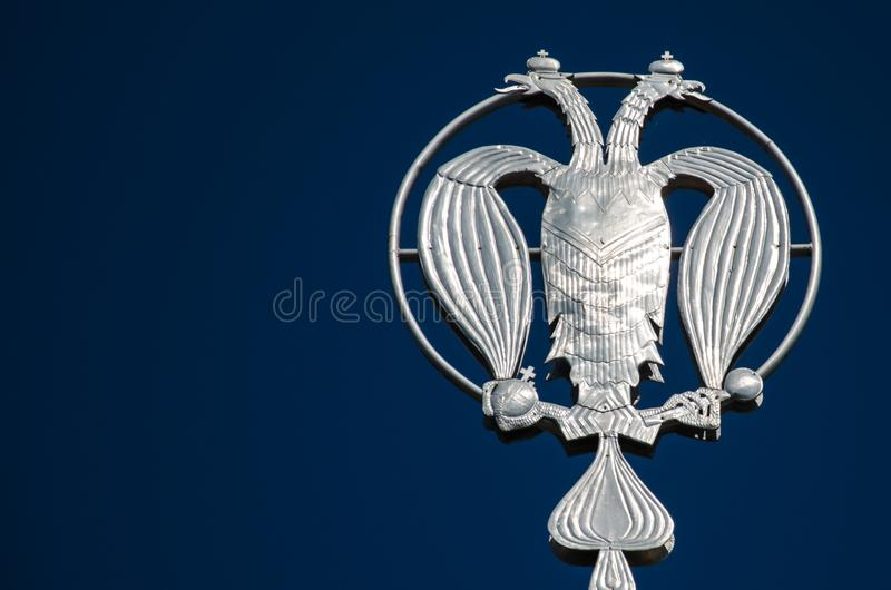 Coat of arms of Russia, silver double-headed eagle against the background of blue sky. Silver Russian heraldic symbol, background. With copy space royalty free stock images