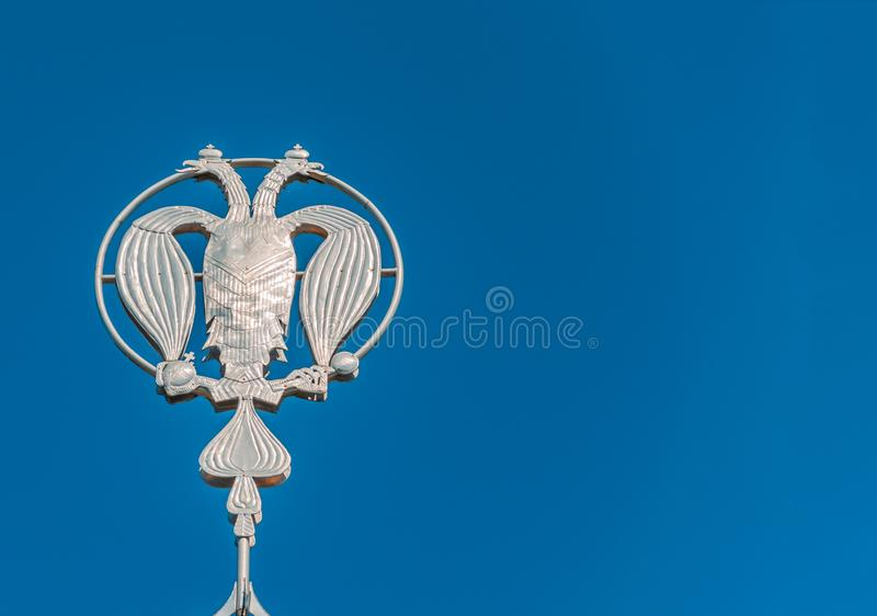 Coat of arms of Russia, silver double-headed eagle against the background of blue sky. Silver Russian heraldic symbol, background. With copy space royalty free stock image