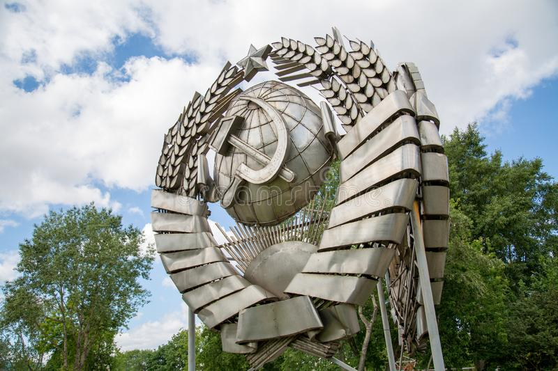 Coat of arms of the USSR made of stainless steel on a background of blue sky trees. royalty free stock photography
