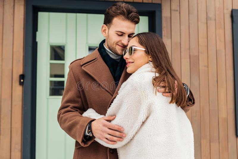 Loving wife wearing beige coat and glasses hugging her beloved royalty free stock photography