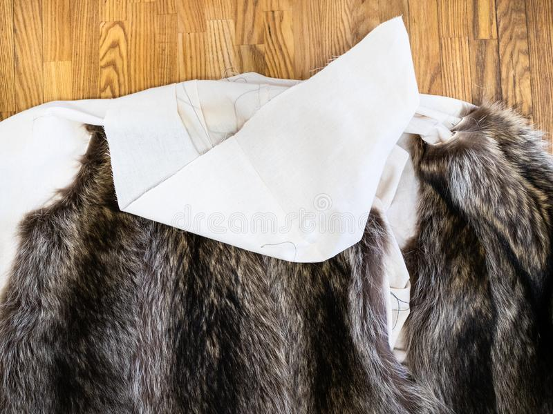 The coat layout with sewn fur pelts on table stock photography