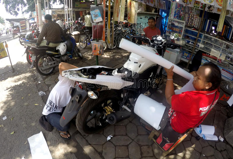 Coat motorcycle. Technicians coat motorcycle body with a sticker in the city of Solo, Central Java, Indonesia royalty free stock photos