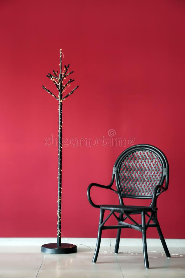 Coat stand with glowing Christmas garland and armchair near color wall indoors stock photos