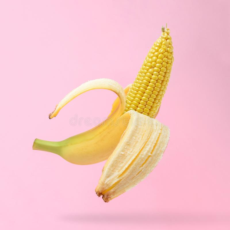 Cob of corn in the peel of banana on pastel pink background. Food creative concept stock images