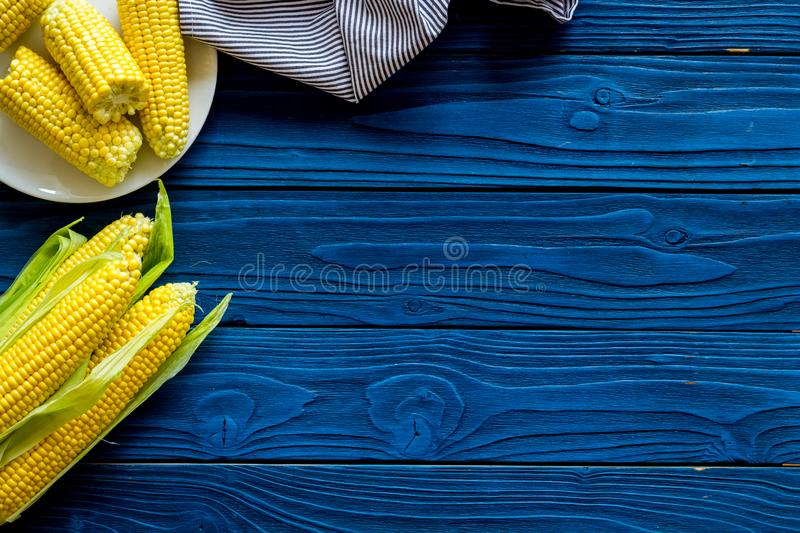 Cob corns and fresh corn on plate on blue wooden background top view mockup royalty free stock image