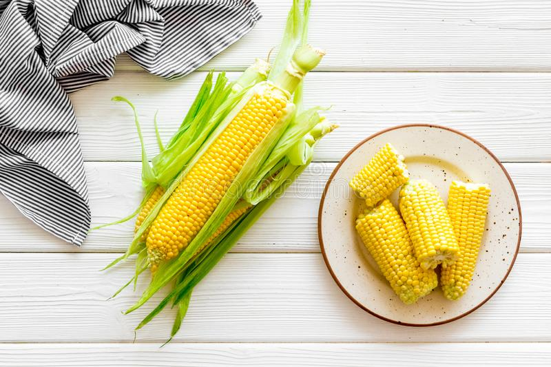Cob corns and fresh corn on plate on white wooden background top view royalty free stock photo