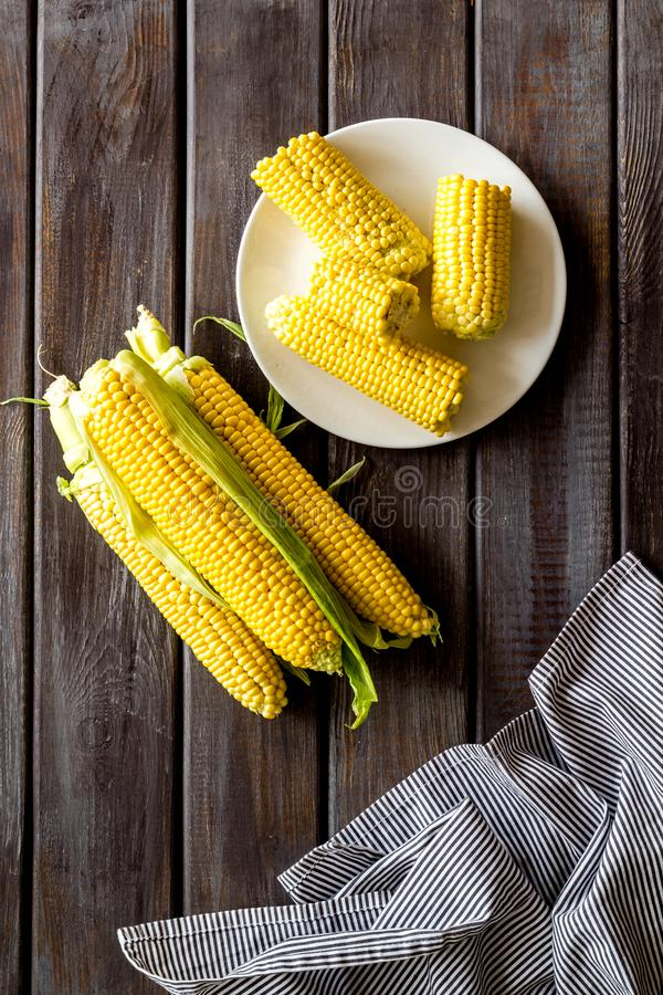 Cob corns and fresh corn on plate on wooden background top view royalty free stock photography
