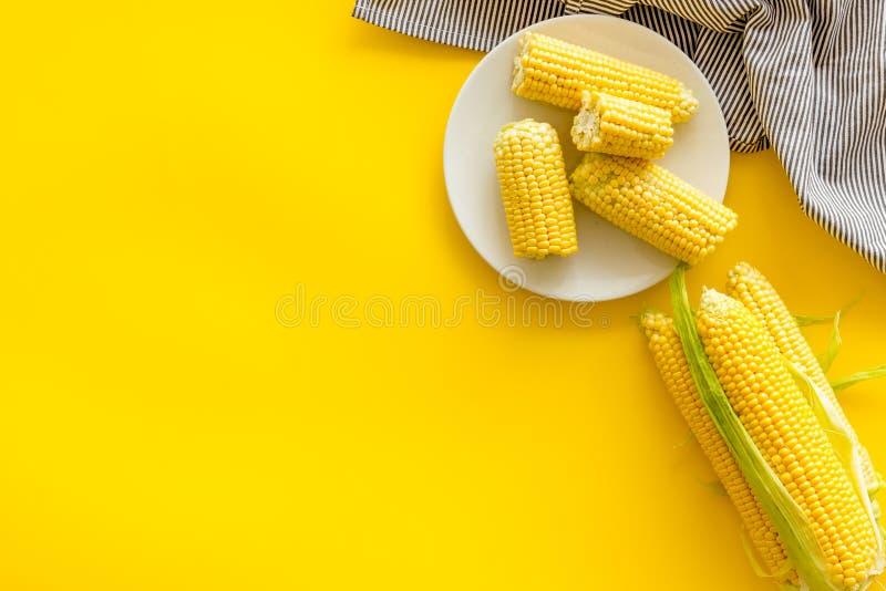 Cob corns och färsk majs på platta på gult bakgrundsvyp fotografering för bildbyråer