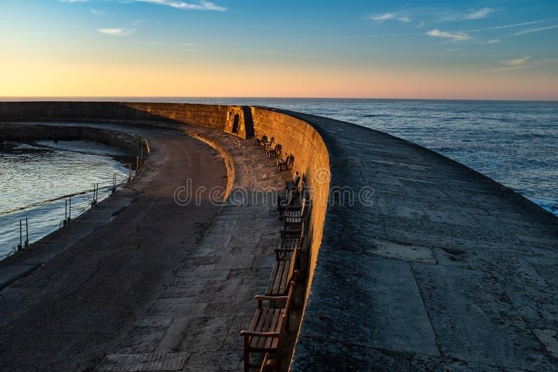 Cobben på Lyme Regis sopar ut till havet, med solen som stiger och glöder för himmel arkivbild