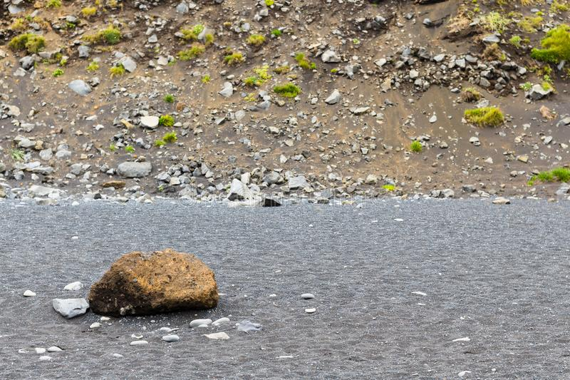 cobble auf Reynisfjara-Strand nahe Steigung des Bergs lizenzfreies stockbild