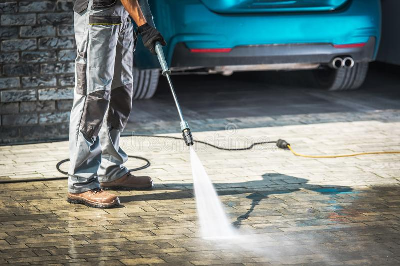 Cobble Driveway Washing. Cobble Driveway Pressure Washing by Caucasian Worker stock photos