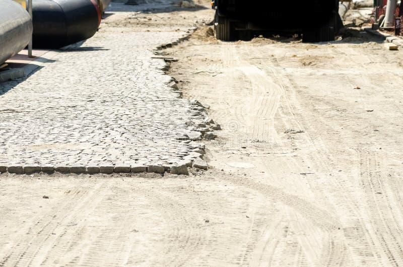 Cobble a pedra de pavimentação na metade da rua no local da reconstrução da cidade fotografia de stock
