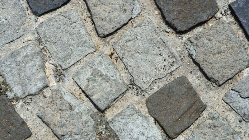 Cobble Steine im Beton auf einem Weg, Hintergrundbeschaffenheitsmakro, selektiver Fokus stockbild