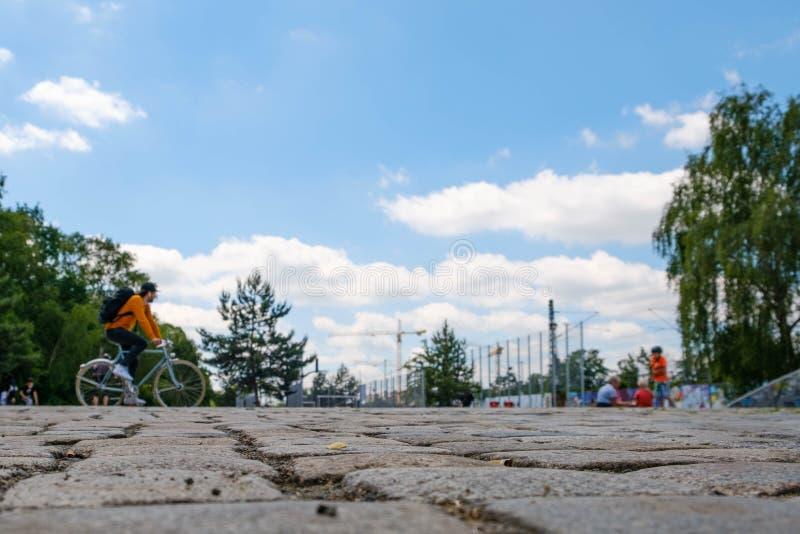 Cobble Steinnahaufnahme mit Leuten im Hintergrund des Parks und des blauen Himmels lizenzfreie stockbilder