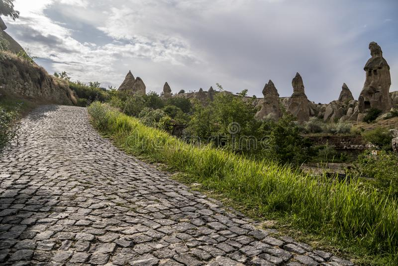Cobble Straße, um Haus von feenhaften Kaminen, die Felsen in Pasabag, sich explosionsartig vermehren Mönch-Tal, Cappadocia, die T stockfotos