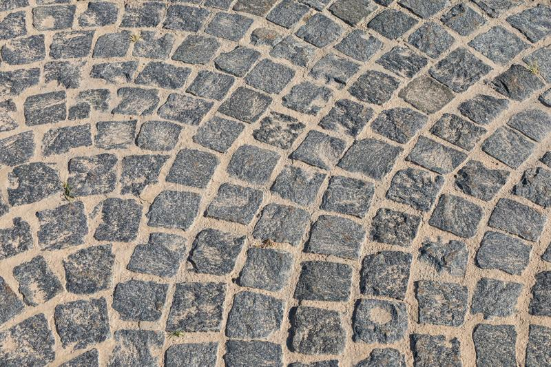 Cobbled road close-up. Pedestrian paving in street. Paved, detail. Brown texture of a paving stone track on sand royalty free stock images