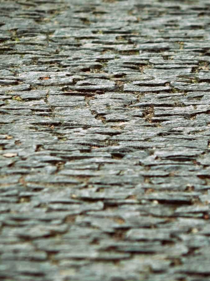 Cobbled road tilt shift focus on the center royalty free stock image