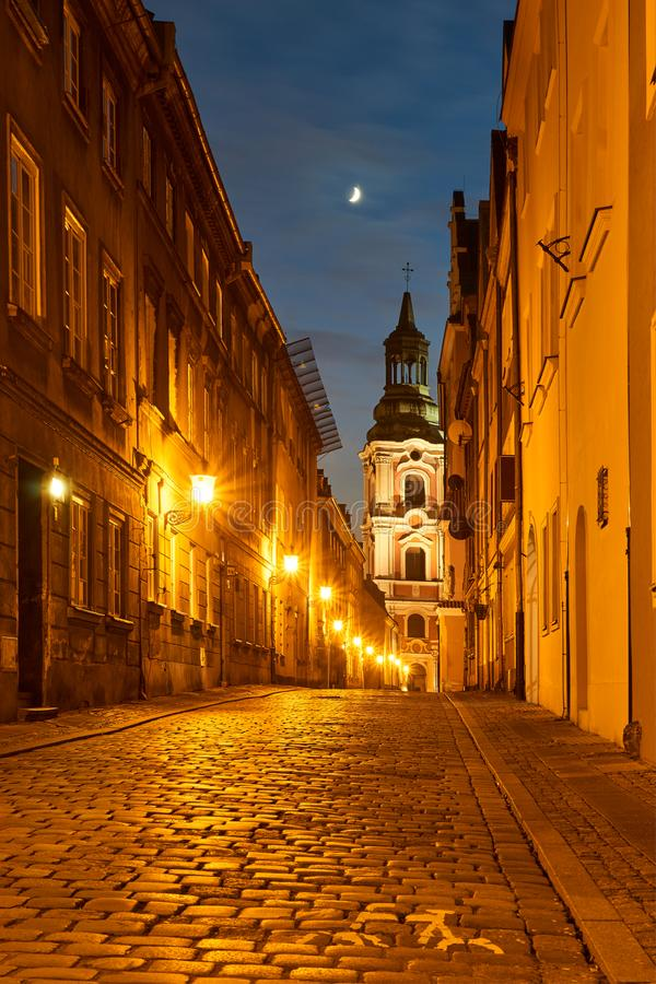 A cobbled street with a baroque belfry of a historic monastery at night. In Pozna royalty free stock photography