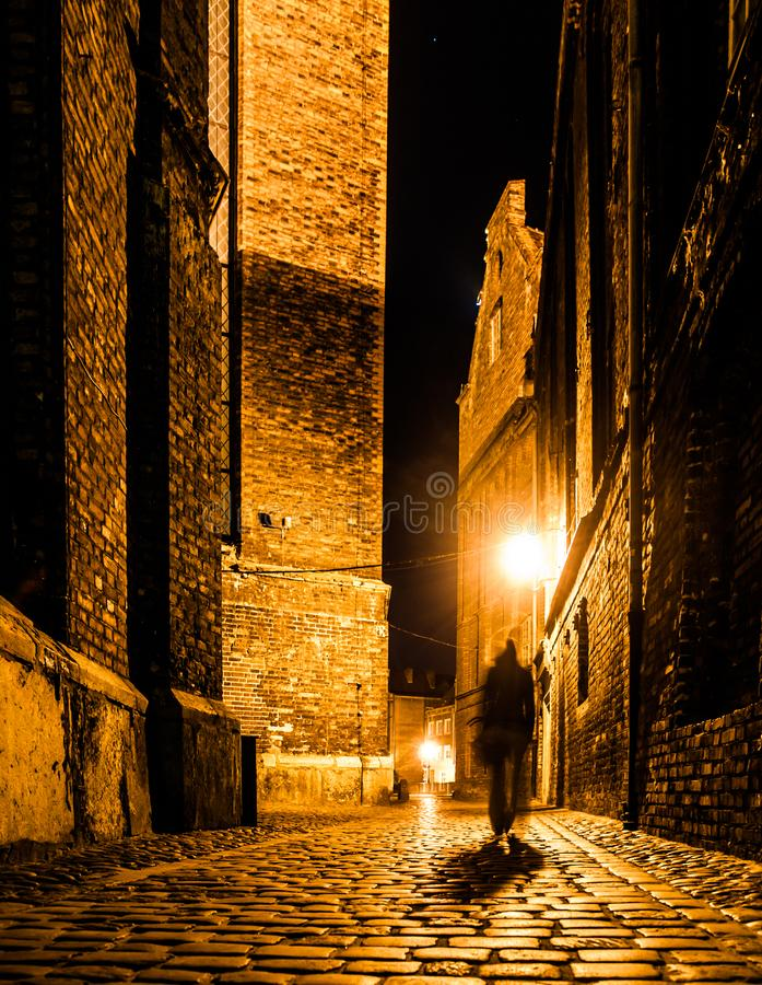 Cobbled street of Old Town with dark blurred silhouette of person. Evokes Jack the Ripper royalty free stock photo