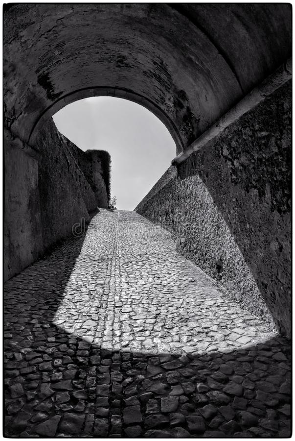 Cobbled Street under cover. Portuguese cobbled street through a tunnel. Black and White street scence stock photography