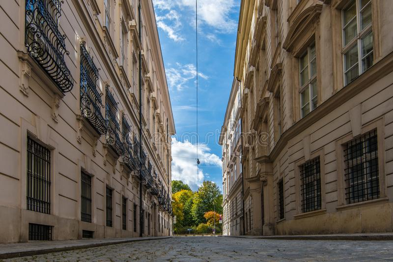 A cobbled Viennese street near to the university, with white clouds and blue sky above. Street light cables run through the frame royalty free stock photos