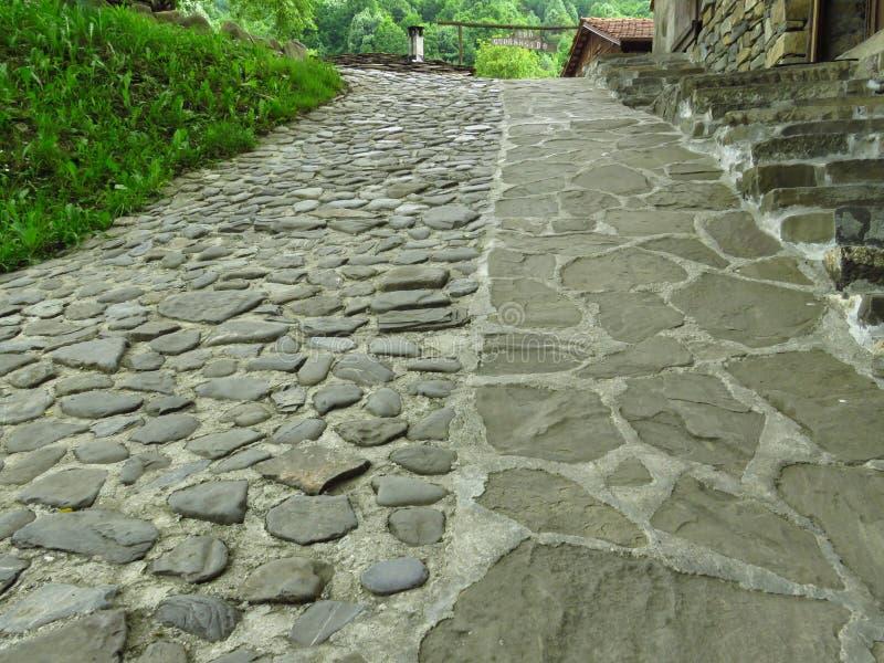 Cobbledstraat en groen gras Grijze straatstenen cobblestones Betonmolens stock afbeelding