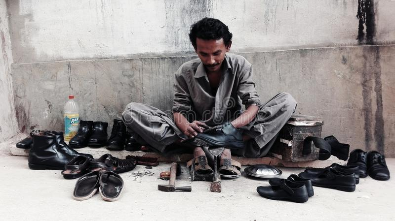 The cobbler. S have played the hardest Job in the world. they mend and polish the shoes and make new shoes for people. they mostly belong to poor families. This stock photos