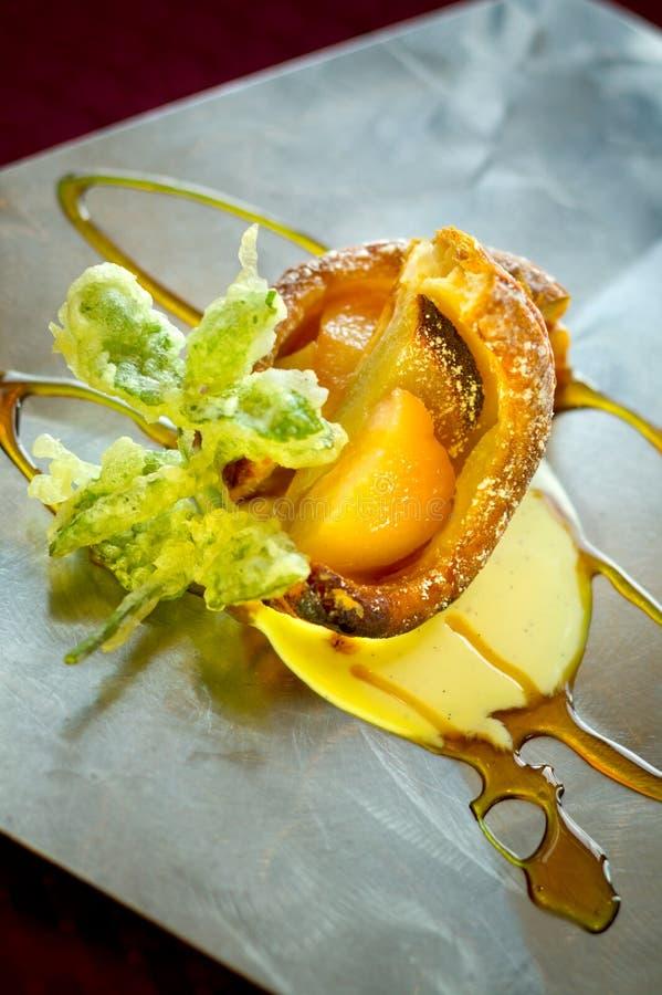 Cobbler/Crumble Dessert With Custard Caramel. A decadent dessert of apple, peach tempura cobbler with sweet sauces on a stainless steel platter stock photo