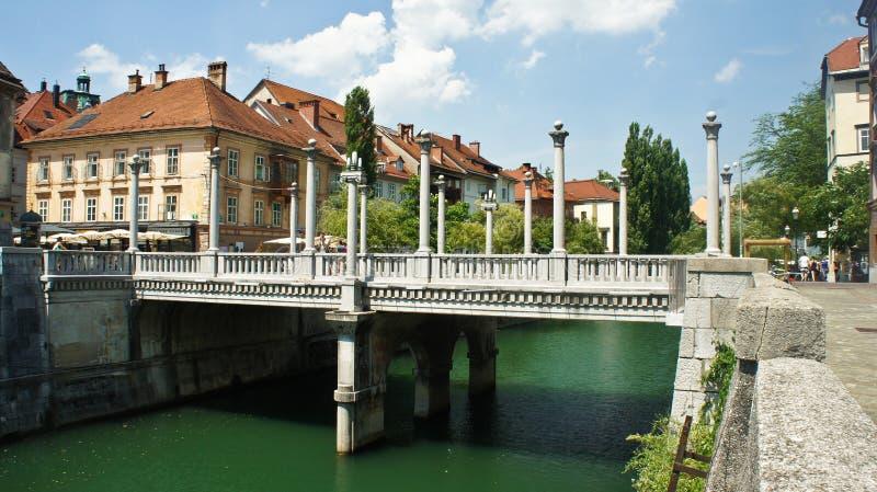 Ljubljana, Slovenia - 07/19/2015 - The Cobbler`s Bridge with Corinthian and Ionic pillars as lamp-bearers, sunny day stock photography