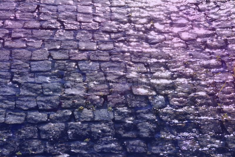 Cobbles. Rough texture of wet block pavement steet , raining day stock images