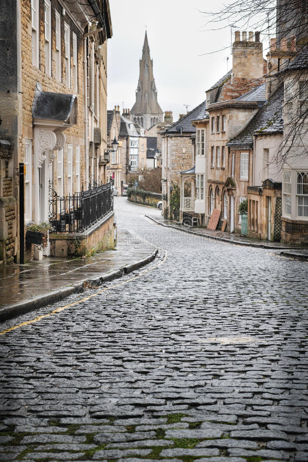Cobbles. Yellow line on a cobbled street in the town of Stamford (England), where most houses are stone built and date from the seventeenth and eighteenth stock image