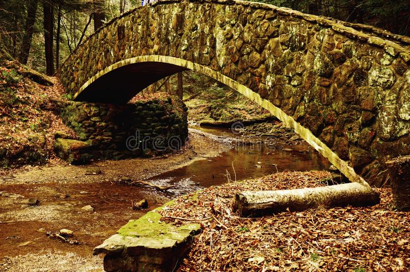 Cobblestone Archway. Mossy cobblestone bridge overpassing a stream at Hocking Hills State Park in Logan, OH stock photo