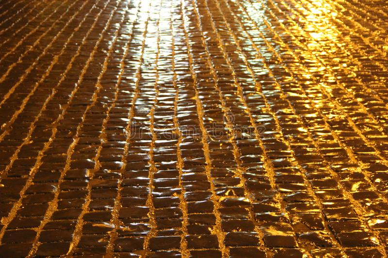 Cobblestone bridge after rain at night in headlight. The cobblestone pavement shines after the rain at night in the headlights royalty free stock images
