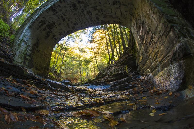 Cobblestone bridge surrounded by fall foliage. A cobblestone bridge spans the length of a creek connecting the two sides of a gorge surrounded by autumn foliage royalty free stock photo