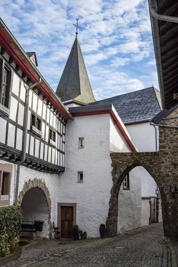 Cobblestone narrow street view with the church tower in Kronenburg, Germany, architectural detail. Cobblestone old narrow street view with the church tower in royalty free stock image